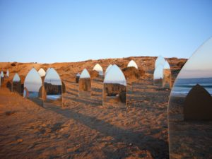 Art installation of mirrors as standing stones on the beach